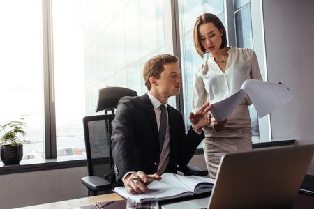 Deux jeunes entrepreneurs analysent les résultats et en discutent. Homme d'affaires avec une collègue féminine, lecture de documents au bureau. Banque d'images