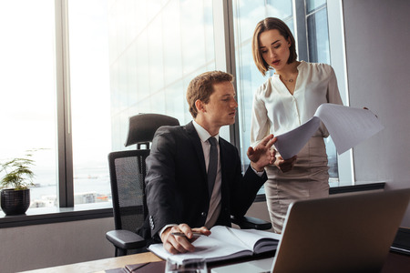Two young business people analyze the results and discuss them. Businessman with female colleague reading documents in office. Stock Photo - 93711705