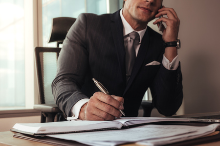 Businessman talking on mobile phone while working at his desk. Man sitting at his desk making notes and talking on mobile phone.