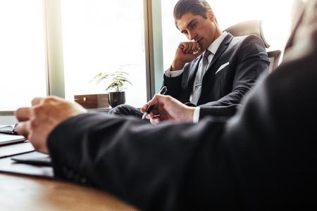 그의 책상에 앉아 및 메모를 만드는 그의 파트너를 찾고 사려 깊은 사업가. 사무실에서 함께 일하는 기업 비즈니스 사람들.