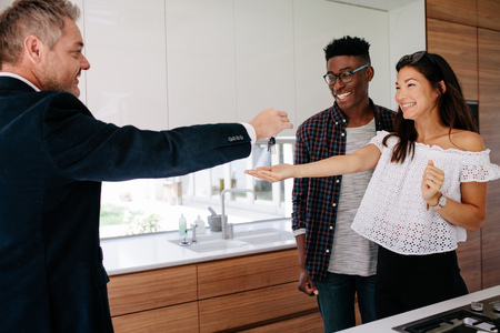 Real estate agent handing over keys of new home to young couple. Happy new property owners with estate broker. Stockfoto
