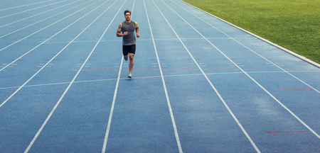 Athlete running on an all-weather running track alone. Runner sprinting on a blue rubberized running track. Stock Photo