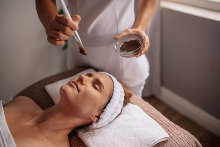 Cosmetologist applying cosmetic mask on the face of the woman in the sap salon.  Woman having spa procedure on her face Фото со стока