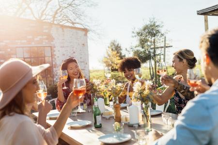 Groep jonge vrienden die uit met dranken hangen bij in openlucht partij. Jonge mannen en vrouwen die een lijst rondhangen die wijn roosteren. Stockfoto