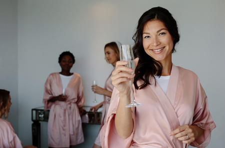 Beautiful young asian woman with champagne celebrating bachelorette party of a friend. Women celebrating hen party in a bedroom.