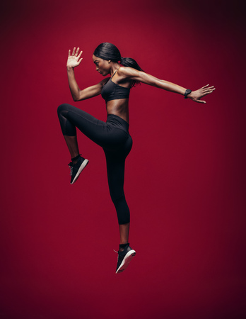 Sports woman doing jumping and stretching workout. Full length of healthy young african fitness woman doing exercise over red background.