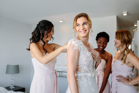 Bride and bridesmaids during the wedding preparations. Friends dressing the bride for wedding in a hotel room. Stock Photo