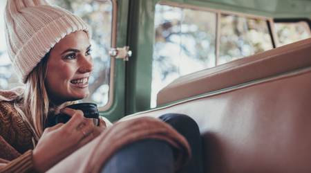 Woman on roadtrip travelling by van. Smiling woman in warm clothing  sitting in back seat of van with cup of coffee.