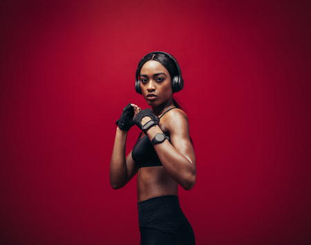 African young woman wearing boxing gloves posing in combat stance looking at camera. Fit young female boxer with headphones ready for fight on red background.
