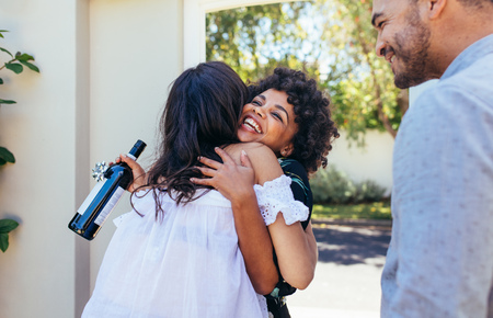 Woman greeting couple for having a new house. Smiling young woman with wine bottle congratulating her friend. Housewarming party with friends. Stockfoto