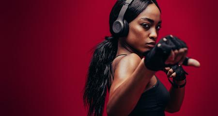 Starke junge Frau mit Kopfhörern , die Boxen übt . Alter weiblicher Boxer , der auf rotem Hintergrund trainiert