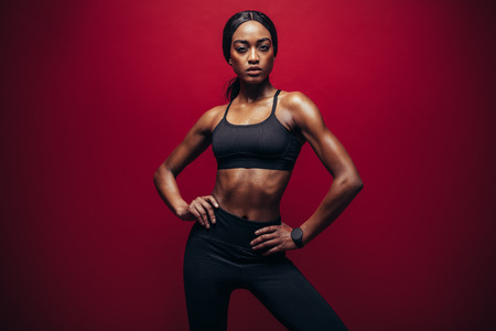 Young woman wearing black sportswear standing against red background. Healthy african woman with perfect muscular body standing in studio.