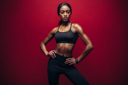 빨간색 배경에 검은 스포츠웨어 서 젊은 여자. 완벽 한 근육 질의 시체와 함께 서있는 건강 한 아프리카 여자.