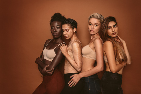 Group of four young diverse girls on brown background. Female models with different skins standing together and looking at camera.