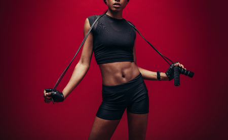 Young woman with a jump rope standing against red background. Female athlete with skipping rope.