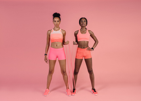Two women doing exercises with resistance band over pink background. Fitness females working out with resistance band. Stockfoto