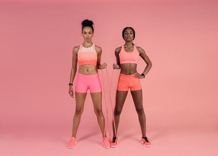 Zwei Frauen, die Übungen mit Widerstandband über rosa Hintergrund tun. Eignungsfrauen, die mit Widerstandband ausarbeiten. Standard-Bild
