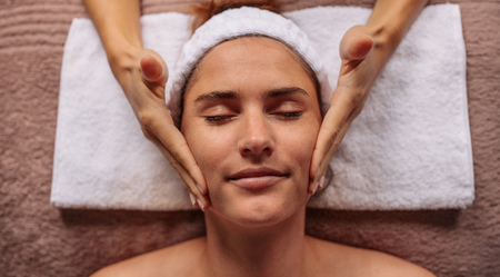 Sluit omhoog van een wijfje die gezicht de schoonheidssalon van de berichtbehandeling krijgen. Mooie jonge vrouw die een gezichtsmassage krijgt. Stockfoto