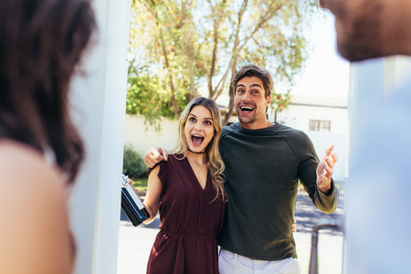 Excited couple at entrance door with bottle of wine. Friends being welcomed by couple at the door. Attending friend's housewarming party. Stockfoto