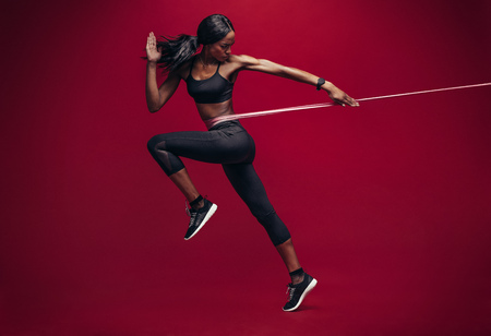 Sporty woman exercising with resistance band on red background. African female athlete working out with elastic bands in studio. Stockfoto