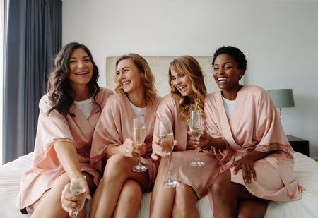 Beautiful bride and happy bridesmaids celebrating hen party with champagne in bedroom. Females in sleeping robe sitting on bed and having champagne.