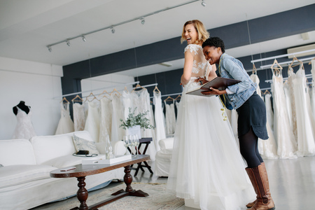 Female trying on wedding gown with women assistant in bridal wear shop. Smiling woman wearing her bridal dress with wedding dress designer in bridal fashion boutique.