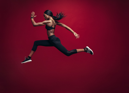 Female athlete running and jumping. Side view shot of healthy african woman working out against red background.