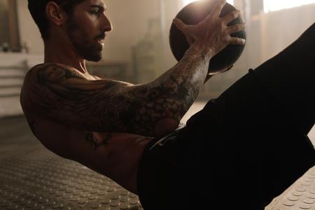 건강 클럽에서 약 공을 근육 질의 남자 운동. 복근을 유지하기 위해 운동 공으로 피트니스 루틴. 스톡 콘텐츠