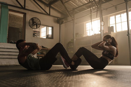 People working out in gym. Fit man and woman doing sit ups together. Stock fotó - 94649599