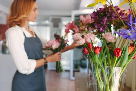 Small business. Female florist unfocused in flower shop. Floral design studio with flowers arranged in vase. Stock Photo