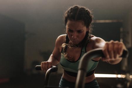 Frau, die stark auf Turnhallenfahrrad trainiert. Frau, die Luftfahrrad für Training an der Turnhalle verwendet.