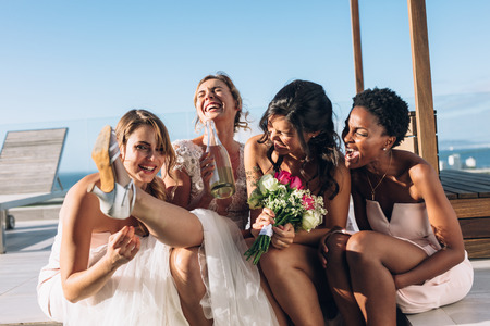 Bride drinking wine while sitting on rooftop with bridesmaids. Bride and bridesmaids having fun before wedding.