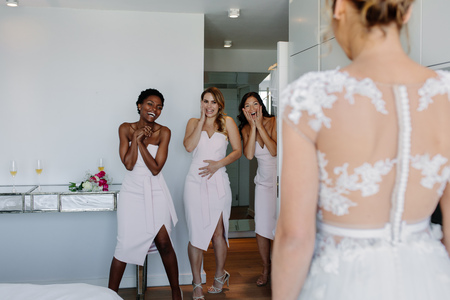 Surprised bridesmaids looking at beautiful bride in wedding gown in hotel room. Wedding morning bridesmaids looking at bride in wedding dress and smiling.