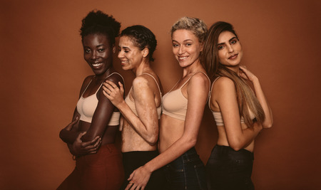 Female models with different skins standing together and smiling. Group of happy young women on brown background. Stok Fotoğraf