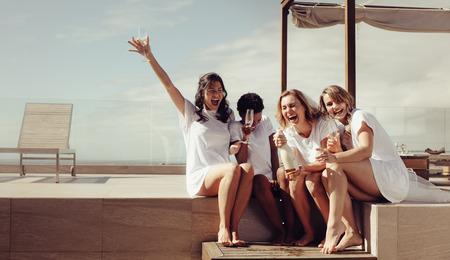 Fiesta de gallina en la azotea. Novia y damas de honor con champán y riendo. Las chicas se están volviendo locas antes de la boda.