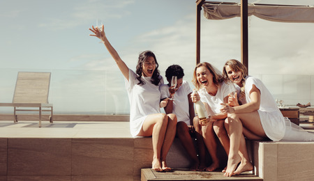 Hen party on the rooftop. Bride and bridesmaids having champagne and laughing. Girls are going crazy before wedding. Stok Fotoğraf
