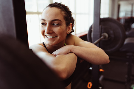 Smiling young woman resting over barbell after training in fitness center. Female taking rest after intense training in gym.