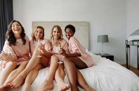 Noiva e damas de honra que comemoram a festa de solteira no quarto. Amigos felizes das fêmeas que sentam-se na cama e que comem o champanhe. Foto de archivo