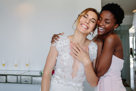 Gorgeous bride in wedding gown having fun with bridesmaid in hotel room. Cheerful bride and bridesmaid on the wedding day. Banco de Imagens