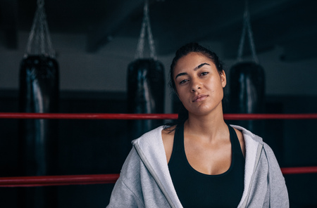 Close up of a female boxer standing inside a boxing ring. Boxer training at a boxing studio.