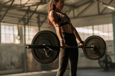 Zdeterminowany i silny trening fitness kobieta z dużymi ciężarami w klubie fitness. Lekkoatletka trzymając sztangę wagi ciężkiej w siłowni.