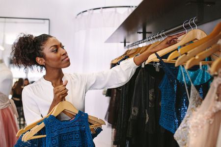 Fashion designer having a look at designer dresses in her fashion studio. Customer selecting dresses in a fashion clothes shop.