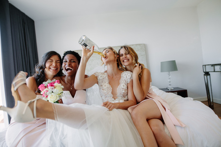 Bride drinking wine while sitting on bed with bridesmaids in hotel room. Bride and bridesmaids having fun in a hotel room before wedding. Stock Photo