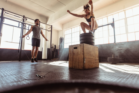 Fit young woman box jumping with man exercising with skipping ropes at a cross training style gym. Young couple training hard at the gym.