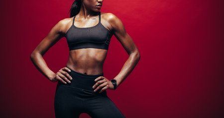 Fit woman in sportswear standing with her hands on hips. Cropped shot of female sports model standing against red background.