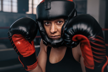 Close up of a female boxer in her boxing gear. Woman boxer at a boxing studio wearing head guard and boxing gloves. Stock Photo