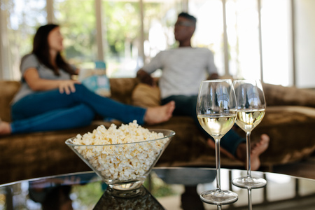 Bowl of popcorn and wine glasses on table in front with couple sitting and relaxing on couch in background.