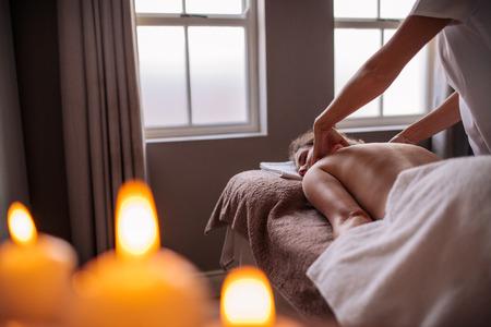 Berufskosmetiker, der zurück Frauen am Badekurortsalon massiert. Frau, die Körpermassage zum Gesundheitsbadekurort empfängt. Standard-Bild