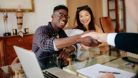 Happy property owners shaking hands with real estate broker after a deal. Young couple handshaking real estate agent after signing contract. Stock Photo