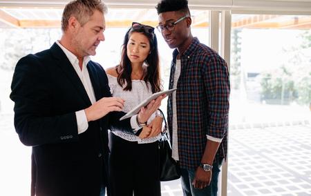 mostrando los términos del contrato en tableta para pareja interracial. Agente de bienes raíces que comparte detalles de la propiedad con los clientes.